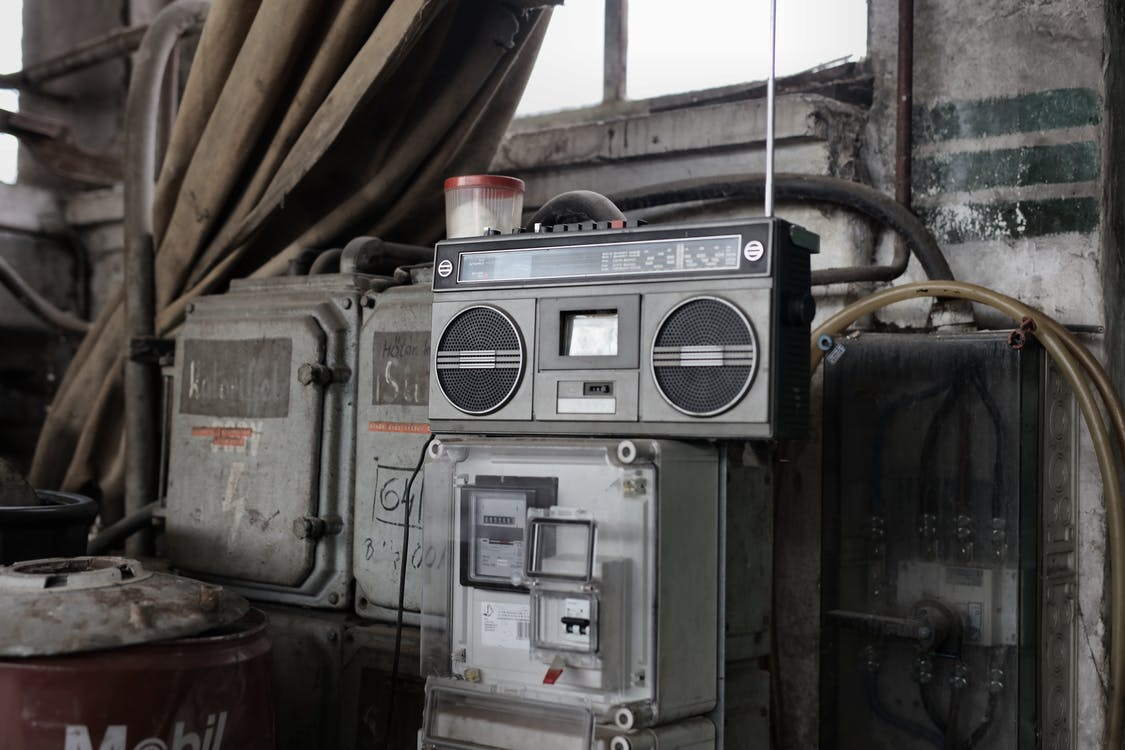 Old fashioned cassette player placed in shabby garage near old industrial equipment
