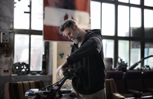 Mature man fixing motorcycle handlebar in garage