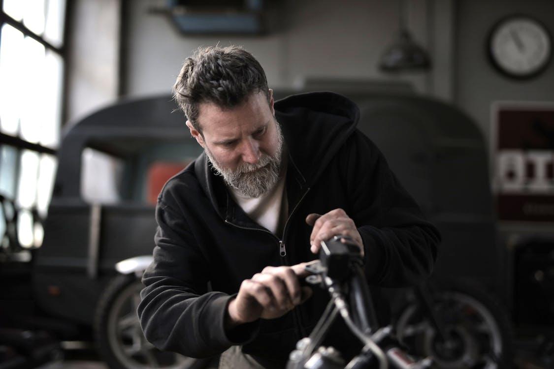 Brutal man repairing motorbike in workshop