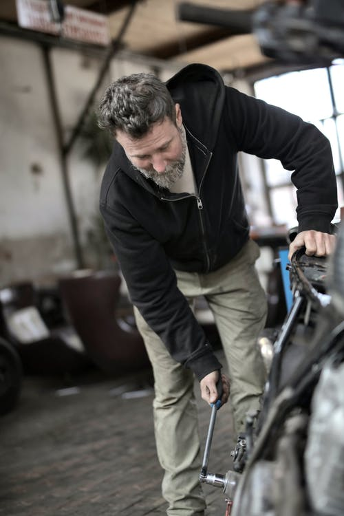 Mature male worker in casual clothes tighten nut with ratchet and repairing mean of transport while working in workshop