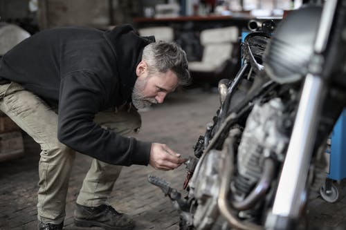 Side view of serious male master in untidy casual clothes standing near motorbike and checking details while working in garage