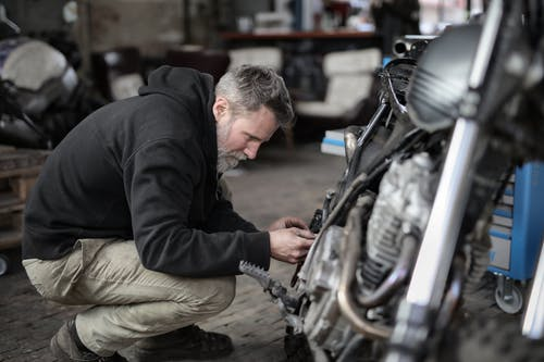 Side view of focused male mechanic in casual wear sitting near motorbike and examining details details in workshop