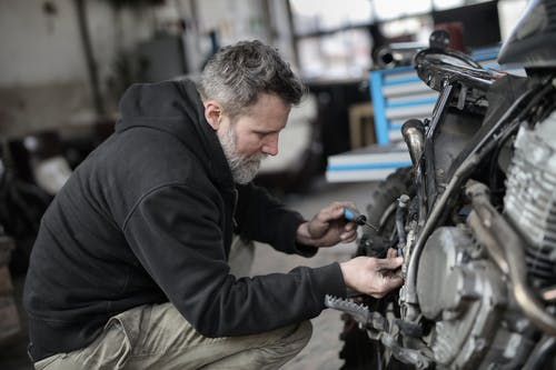 Bearded man fixing motorcycle in workshop