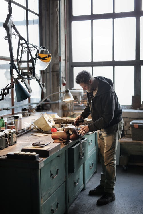 Side view of bearded male master in casual clothes standing at workbench and fixing details with professional metal instrument