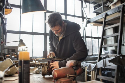 Focused male mechanic using spray paint on metal detail