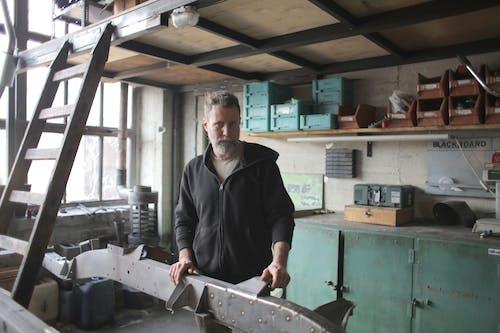 Brutal male mechanic in shabby workshop
