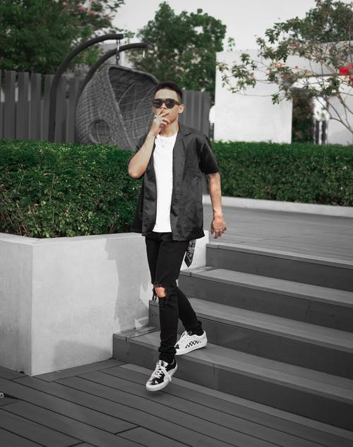 Unrecognizable guy in trendy outfit and sunglasses walking down stairs