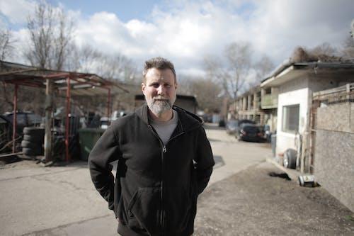 Smiling male mechanic standing near garage
