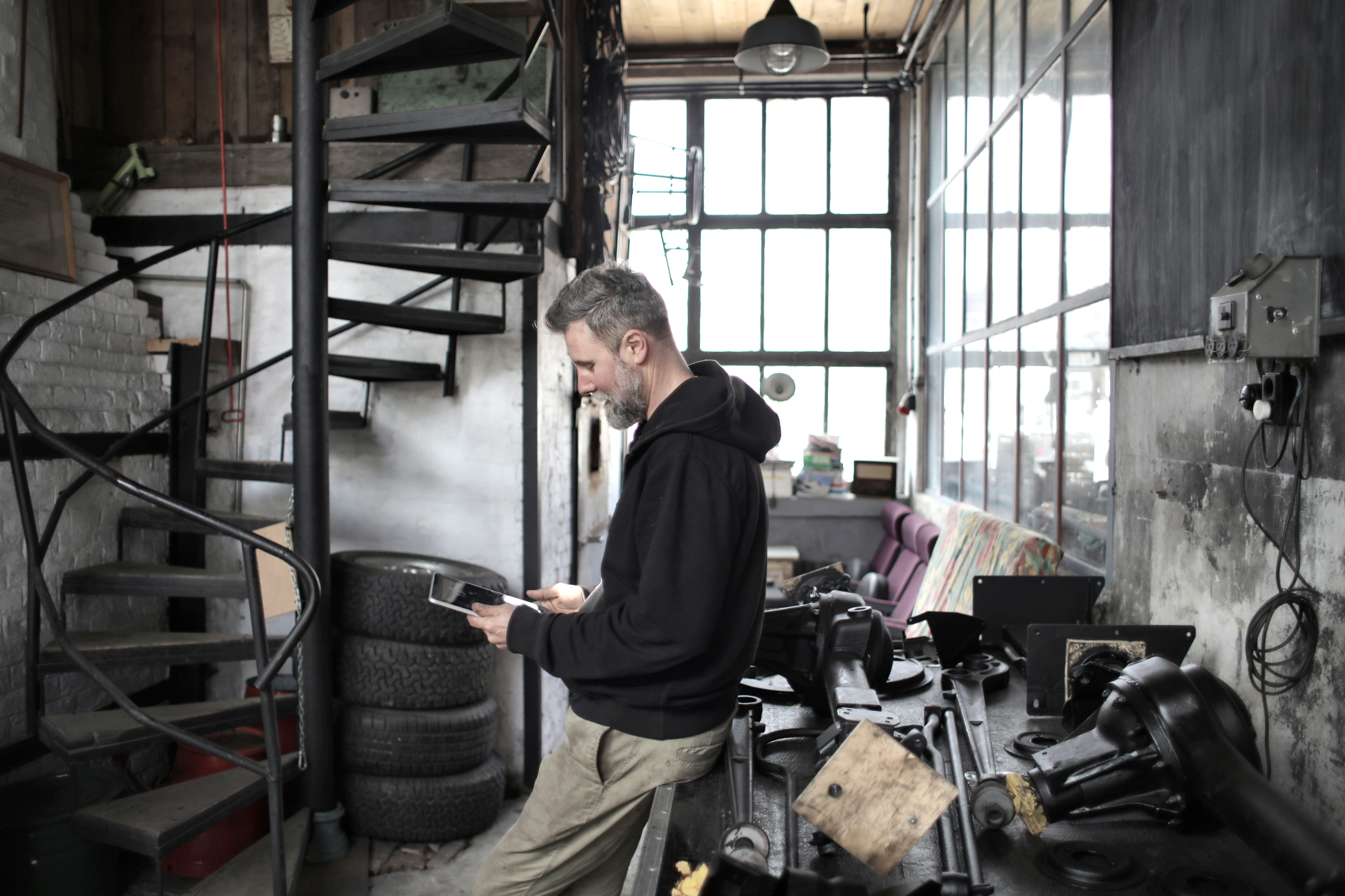 bearded worker using tablet while standing near workbench in workshop