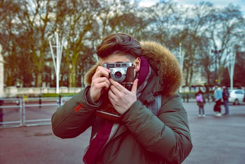 Woman in Red Parka Jacket Holding Camera