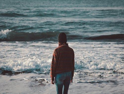 Woman in Brown Jacket Standing on Seashore