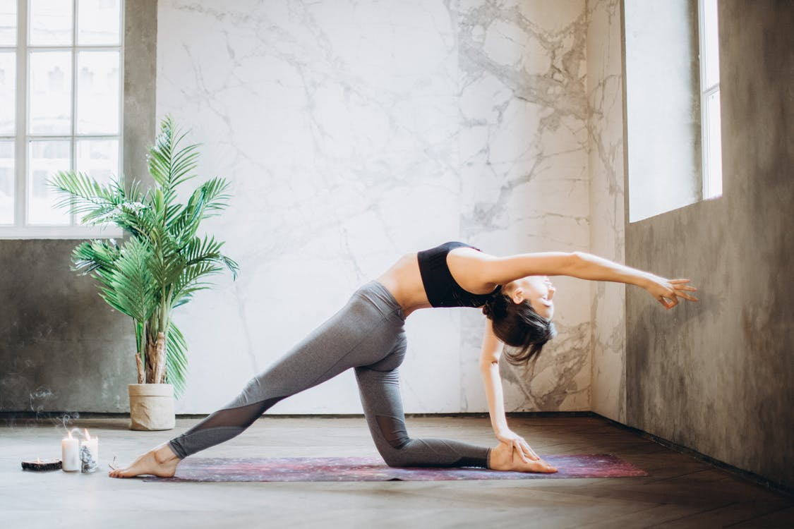Woman in Gray Leggings and Black Sports Bra Doing Yoga on Yoga Mat