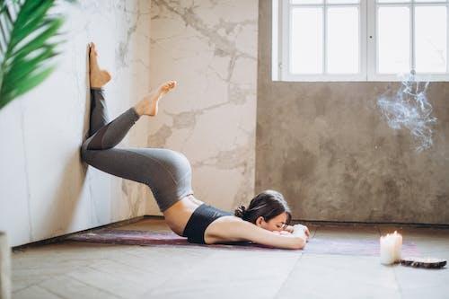Vrouw In Grijze Beenkappen En Zwarte Tanktop Die Op Yogamat Liggen Die Yoga Doen
