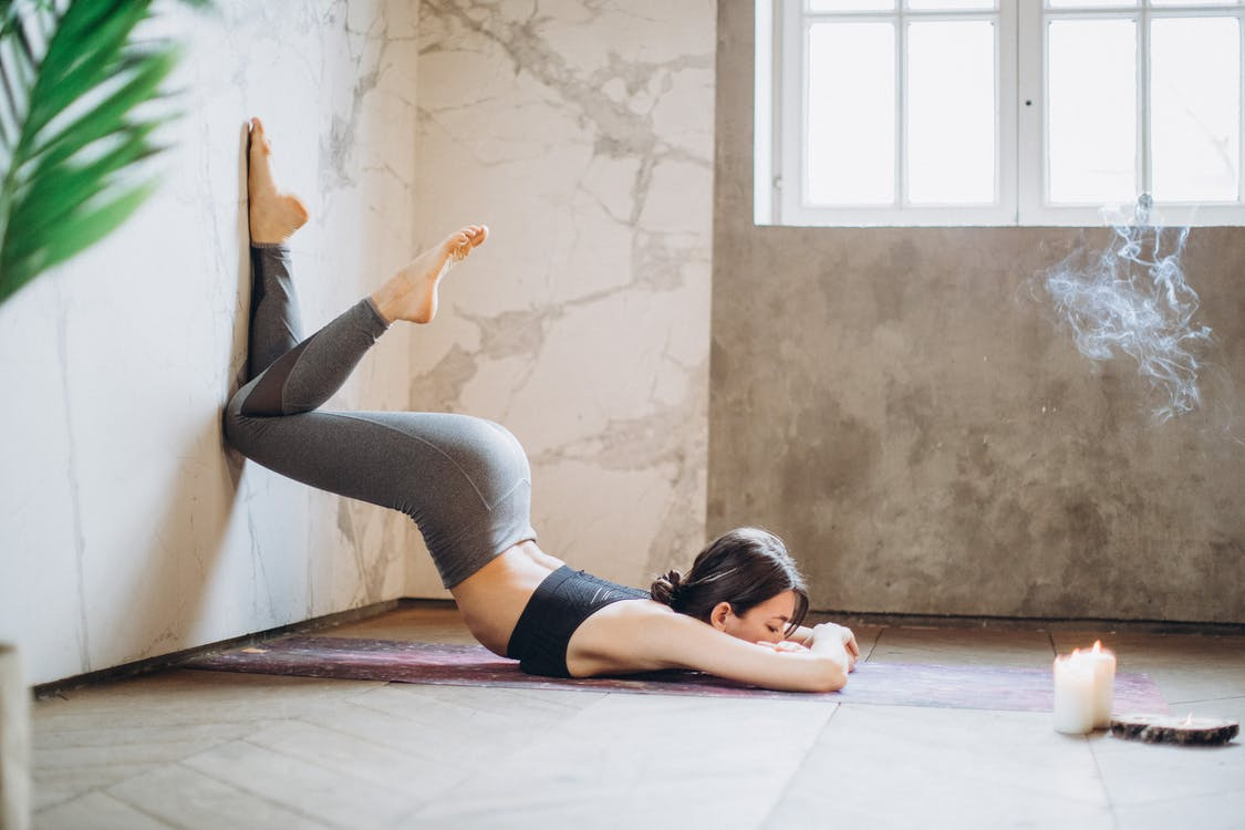 Woman in Gray Leggings and Black Tank Top Lying on Yoga Mat Doing Yoga