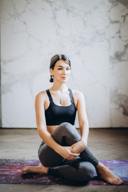 Woman in Black Tank Top and Black Leggings Sitting on Floor