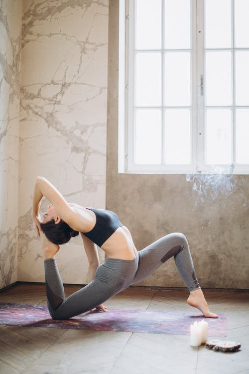 Woman in Black Sports Bra and Gray Leggings Doing Yoga