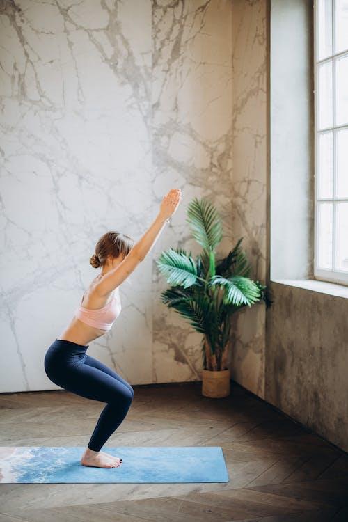 白色背心和黑色緊身褲,在瑜伽墊上做瑜伽的女人