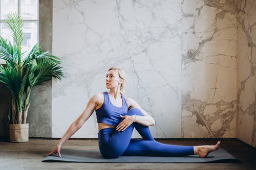 Woman in Blue Tank Top and Blue Leggings Doing Yoga