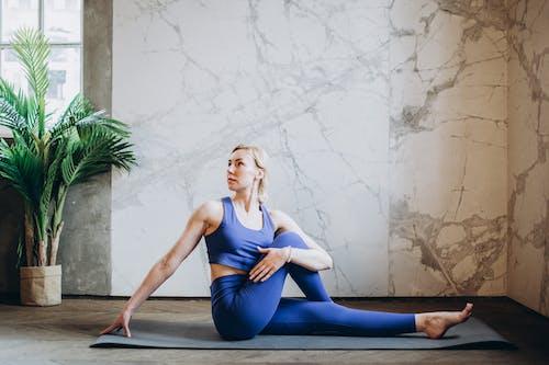 Frau Im Blauen Trägershirt Und In Den Blauen Leggings, Die Yoga Tun