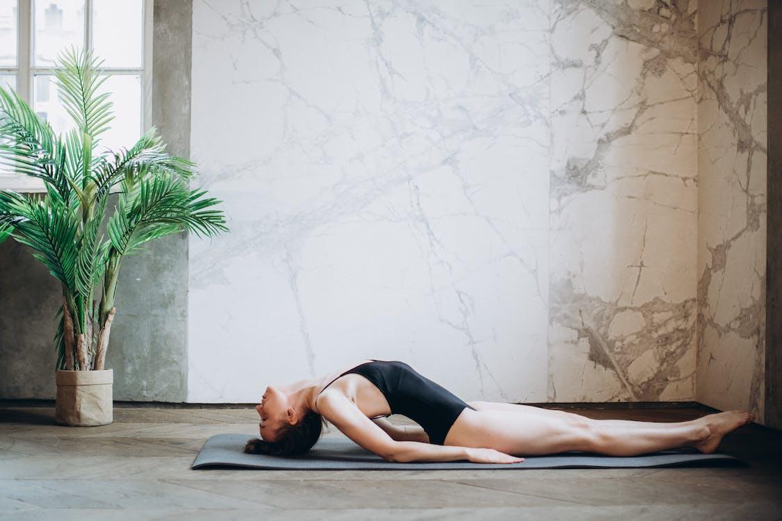 Woman Lying on Gray Yoga Mat