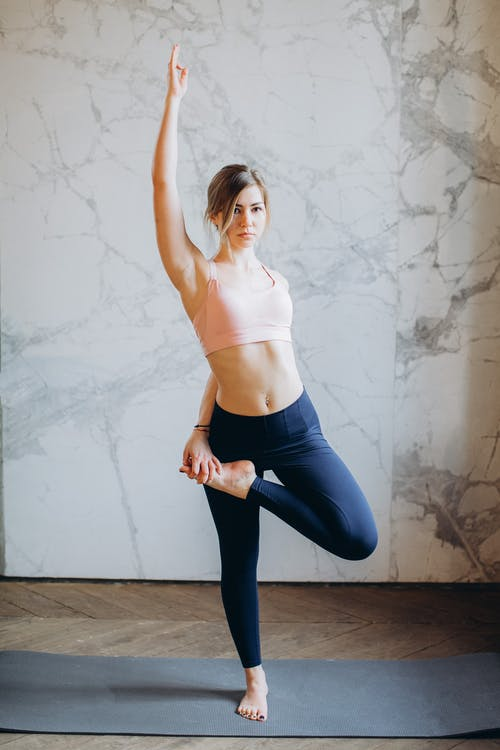 Woman in Pink Tank Top and Blue Leggings Doing Yoga