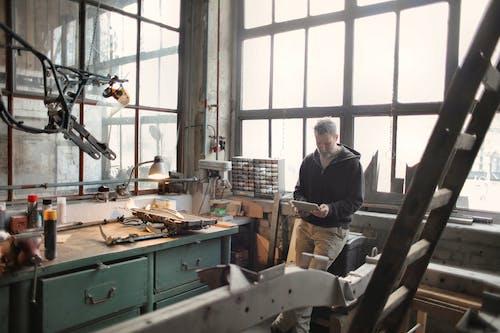 Bearded male worker using tablet while standing near window in workshop