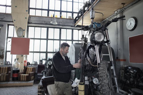 Side view of bearded adult mechanic in casual uniform standing near motorcycle and working with engine in workshop