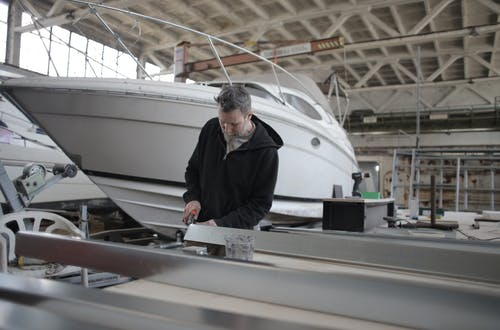 Concentrated bearded adult workman in casual wear working with metal detail near boat in garage