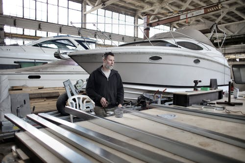 Focused adult worker preparing metal details in workshop with yachts