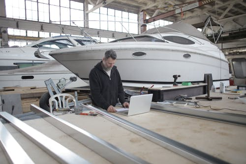 Adult worker using laptop at workbench during work in boat garage