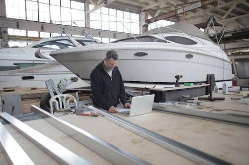 Travailleur Adulte à L'aide D'un Ordinateur Portable à L'établi Pendant Le Travail Dans Un Garage à Bateaux