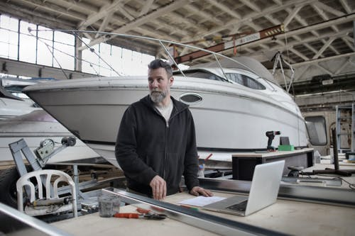 Adult bearded man in casual clothes using laptop while working with metal details near boat in workshop and looking away