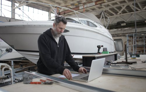 Thoughtful adult worker using laptop while working with metal parts near boat in workshop