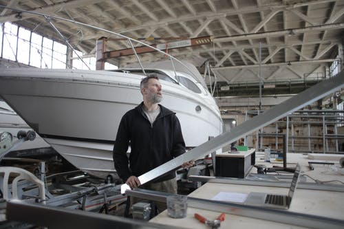 Side view of adult bearded workman in casual clothes standing near workbench and controlling metal detail in garage with yachts