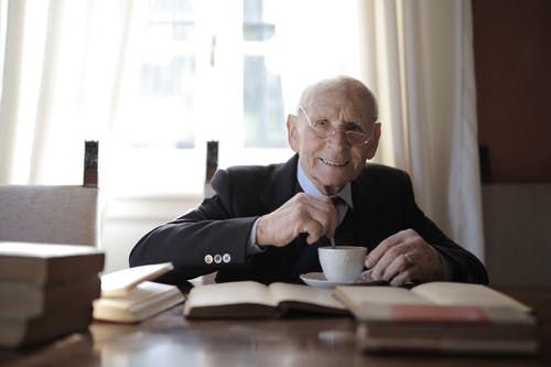 Senior man in formal suit drinking hot drink while sitting at table with book
