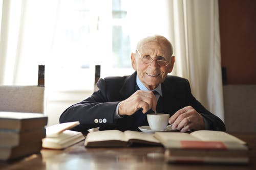 Senior man drinking hot beverage while reading book at table in light room