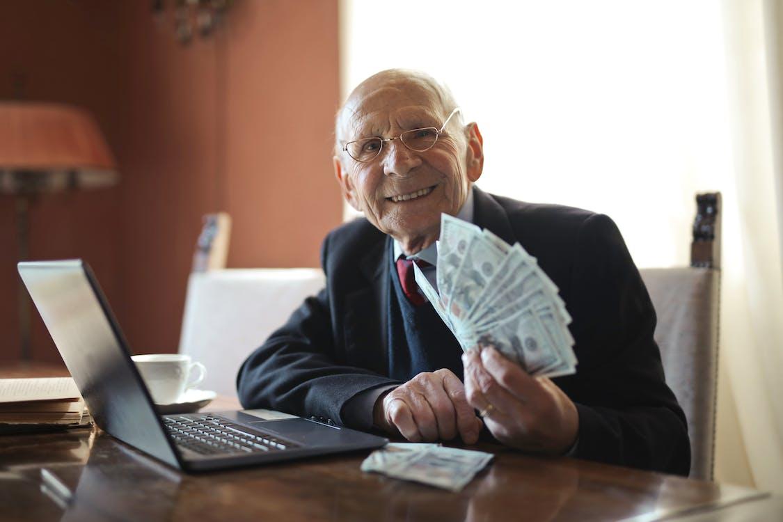 Pengusaha Senior Yang Bahagia Memegang Uang Di Tangan Saat Mengerjakan Laptop Di Meja