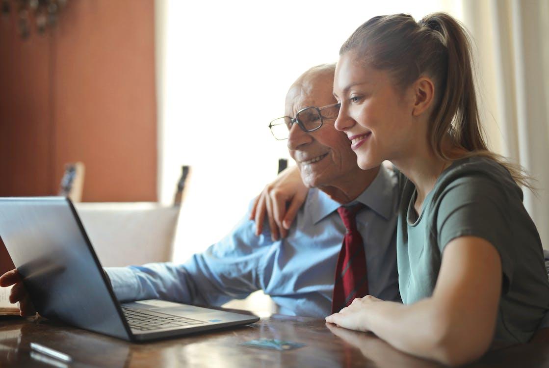 Genç Pozitif Kadın Dizüstü Bilgisayar Kullanan Kıdemli Adama Yardım