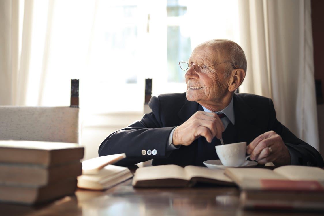 Positive senior man in formal suit and eyeglasses drinking hot beverage from cup while sitting at wooden table with books and looking away
