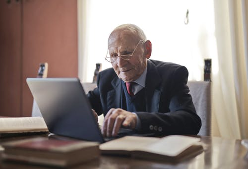 Focused elderly man in formal black suit and eyeglasses using laptop while sitting at wooden table with books in light room