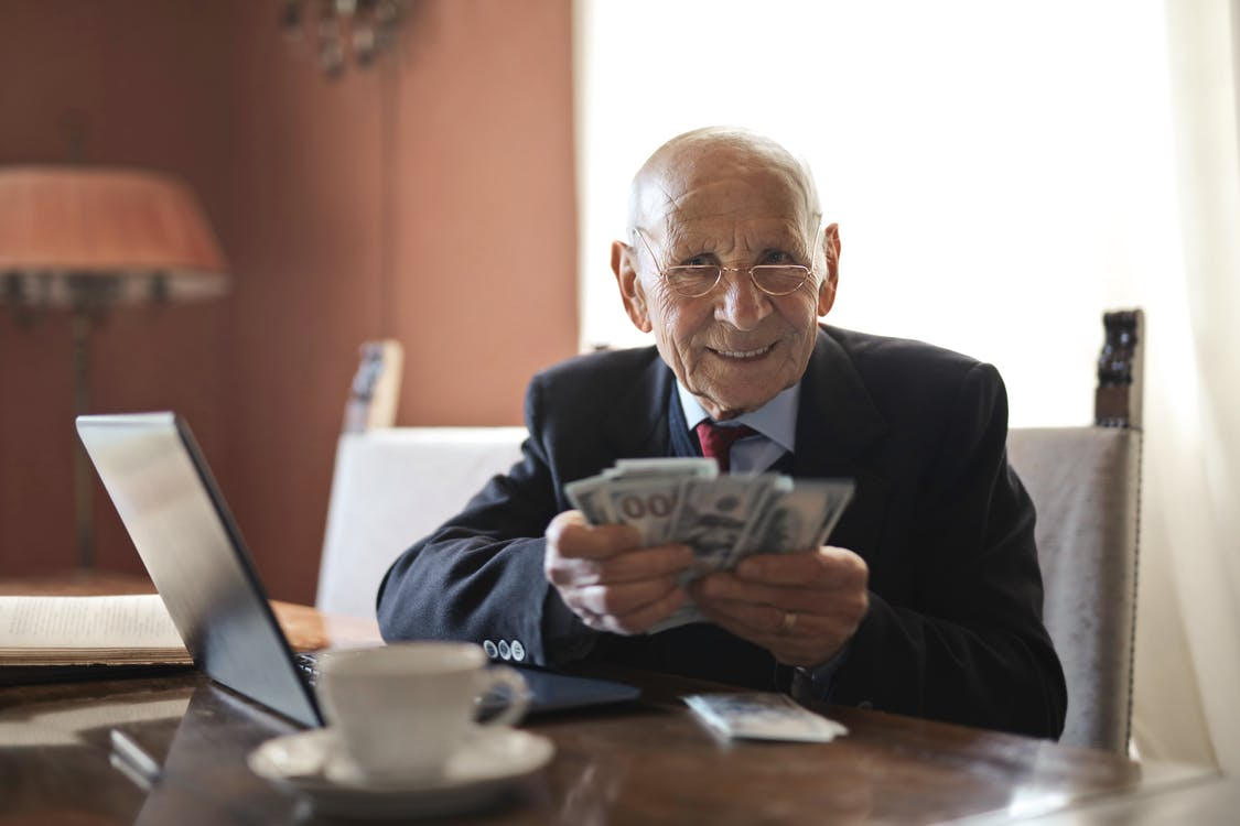 Confident senior businessman holding money in hands while sitting at table near laptop