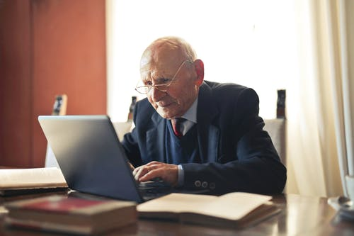 Serious senior man in formal suit working on laptop at workplace