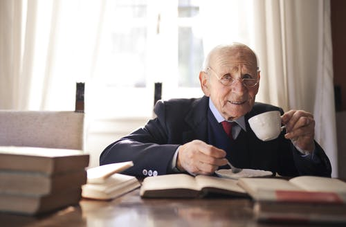 Confident senior man drinking hot beverage while sitting at table with books