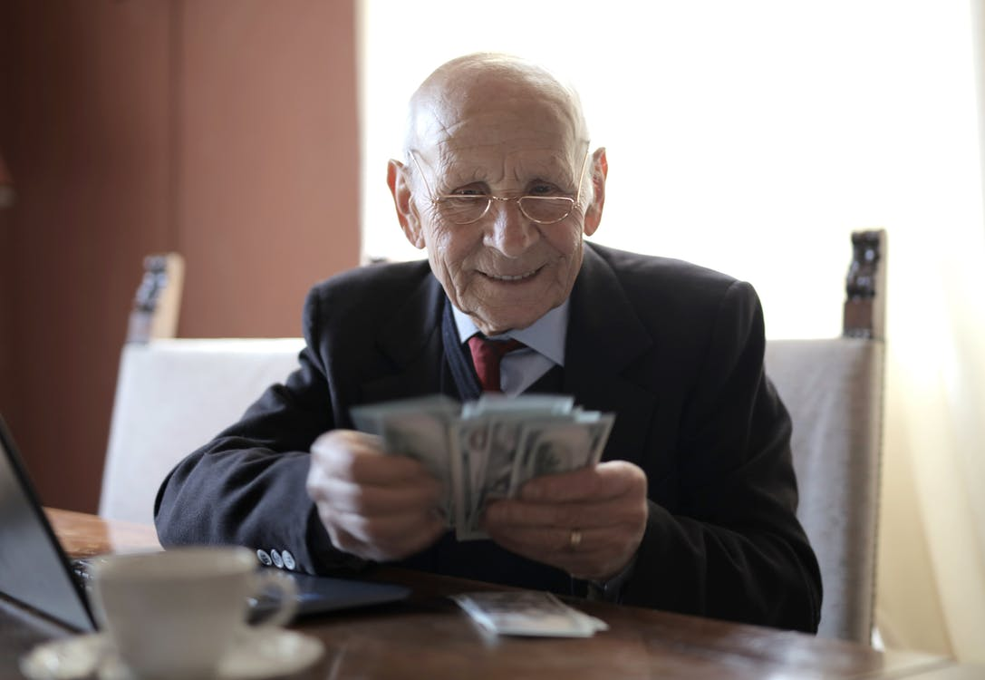 Positive senior businessman in formal suit and eyeglasses counting money bills while sitting at wooden table with cup of beverage and near opened laptop