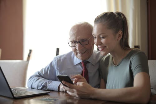 Smiling young woman in casual clothes showing smartphone to interested senior grandfather in formal shirt and eyeglasses while sitting at table near laptop