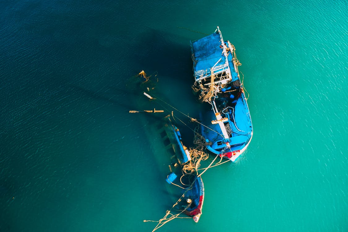 From above picturesque view of boats floating in ocean bright green water in daylight