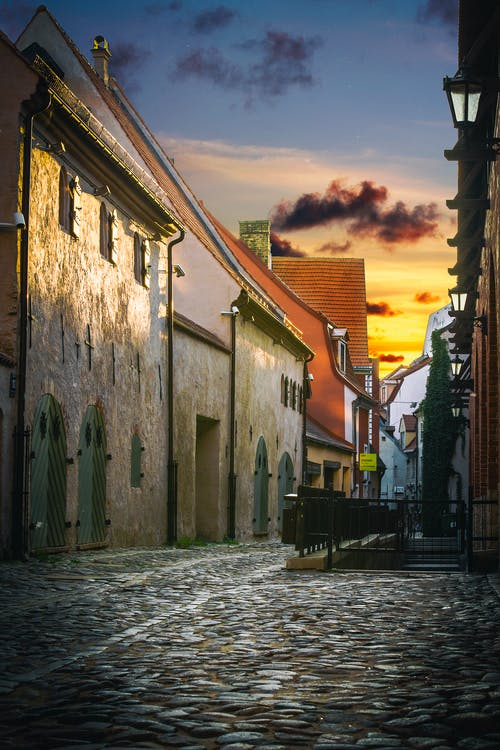 Cobblestone pathway between building facades at colorful sunset in evening