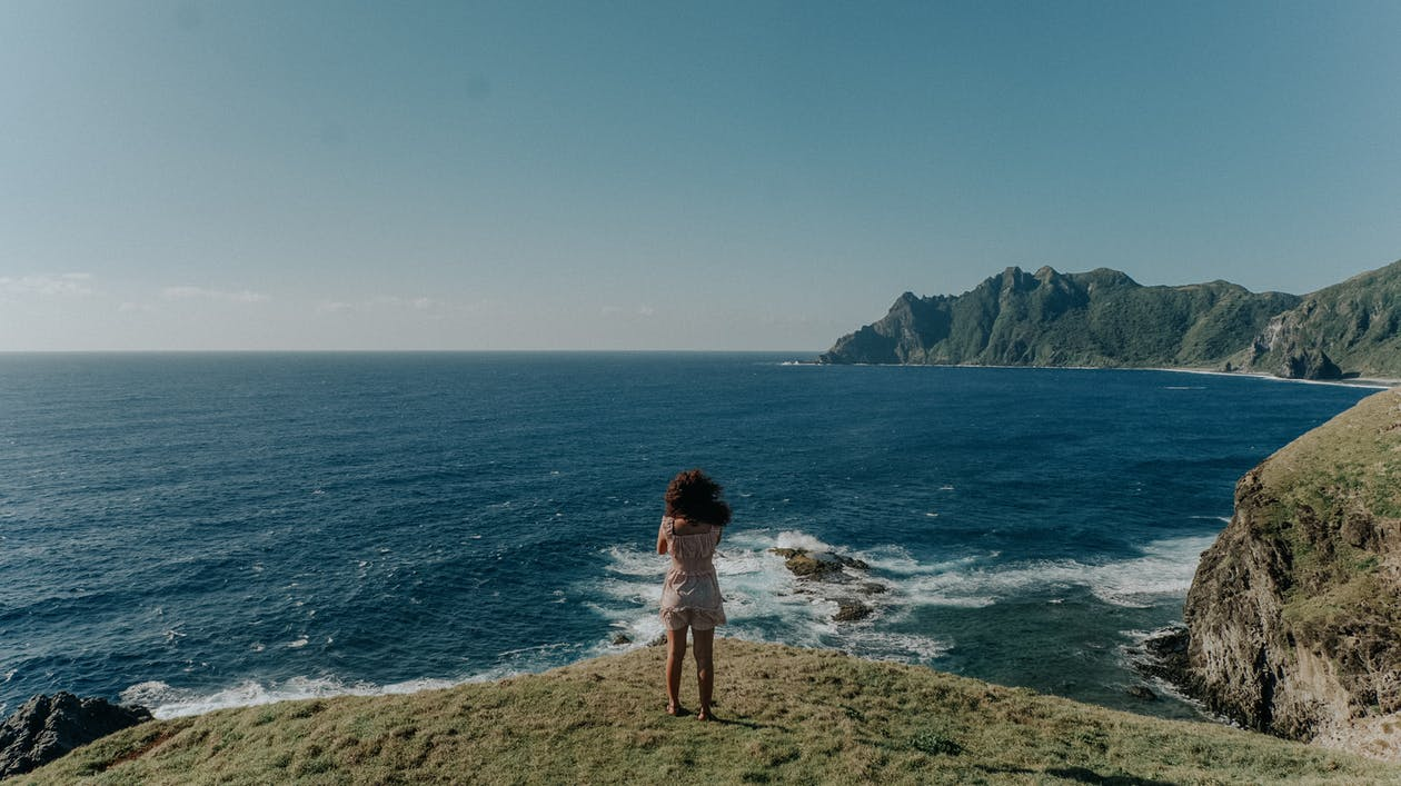 Back View Photo of Woman in White Top and Shorts Standing on Cliff Near Body of Water