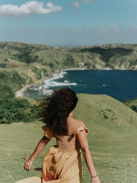 Woman in Brown Sleeveless Dress Standing on Green Grass Field