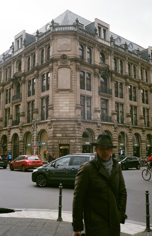 Man in Green Jacket Wearing Hat Standing on the Street Near Cars and Building